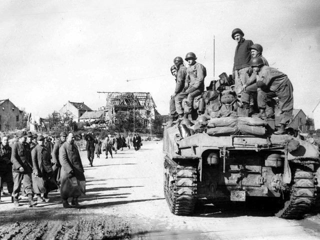 American troops on a tank, heading into the city of Aachen, Germany, on Oct. 15, 1944, as a group of German prisoners under guard and another group of refugees head away from the fighting. (AP Photo)