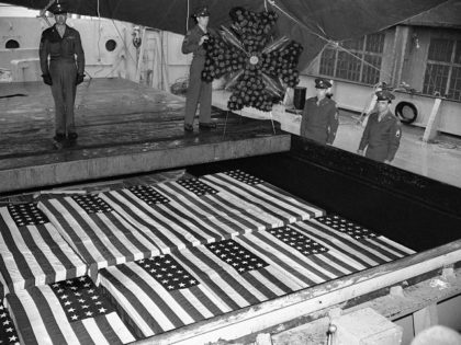 As three others stand at attention, a soldier places a wreath from Veterans of Foreign Wars, on the hold over flag-draped caskets of Americans who gave their lives during the war in Europe, following the arrival of the S.S. Lawrence Victory at the Brooklyn (N.Y.) Army Base on May 7, …
