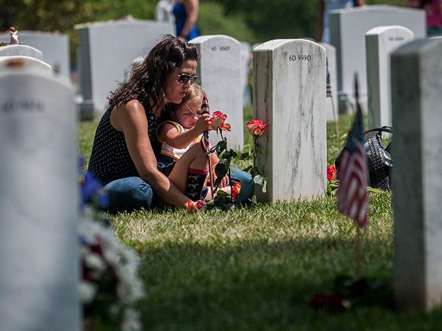 Angela Spraul and her daughter Ava, 4, sit at the grave of her husband John Spraul, U.S. Navy, who died Feb. 28, 2013, at Section 60 on Memorial Day at Arlington National Cemetery on May 25, 2015 in Arlington, Va. (Photo by Gabriella Demczuk/Getty Images)