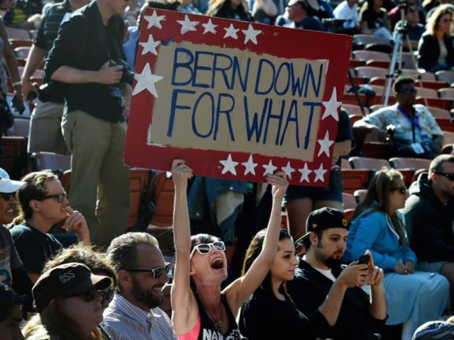 A supporter holds a sign as US Democratic presidential hopeful Bernie Sanders speaks at an election rally in Irvine, California on May 22, 2016. / AFP / Mark Ralston (Photo credit should read MARK RALSTON/AFP/Getty Images)