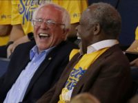 Democratic presidential candidate Sen. Bernie Sanders, I-Vt., left, laughs with actor Danny Glover during Game 7 of the NBA basketball Western Conference finals between the Golden State Warriors and the Oklahoma City Thunder in Oakland, Calif., Monday, May 30, 2016.