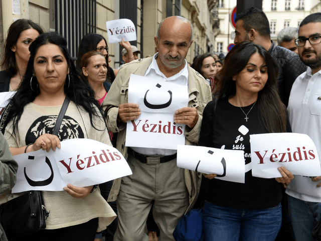 Demonstrators hold signs reading 'Yezidis' and the arabic letter 'N', which stands for Christian, as they take part on August 13, 2014 in a demonstration in support of the Yezidis and the Christians in Iraq, near the French Elysee presidential palace in Paris.