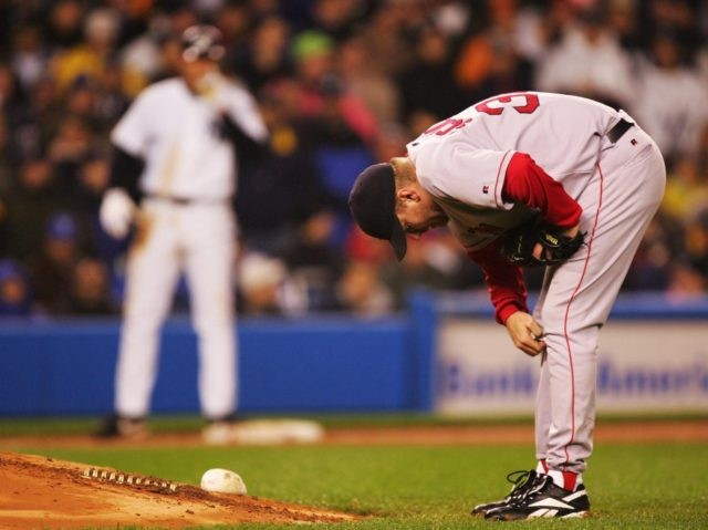 NEW YORK - OCTOBER 19: Pitcher Curt Schilling #38 of the Boston Red Sox takes a look at his foot as Alex Rodriguez #13 of the New York Yankees stands on third base in the fourth inning during game six of the American League Championship Series on October 19, 2004 …