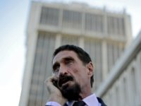 US anti-virus software pioneer John McAfee speaks on his mobile phone in front of the Supreme Court in Guatemala City on December 04, 2012. McAfee, wanted for questioning over the murder of his neighbor last month in Belize, is seeking political asylum in Guatemala. AFP PHOTO / Johan ORDONEZ (Photo …