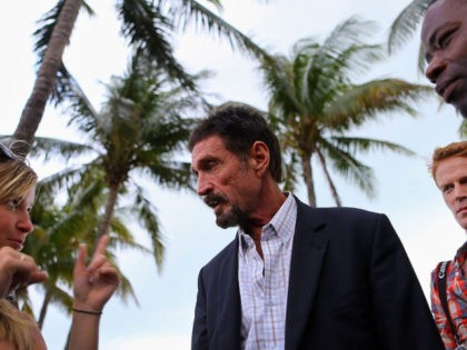 """MIAMI BEACH, FL - DECEMBER 13: John McAfee interacts with people after speaking to reporters outside of the Beacon Hotel where he is staying after arriving last night from Guatemala on December 13, 2012 in Miami Beach, Florida. McAfee is a """"person of interest"""" in the fatal shooting of his …"""