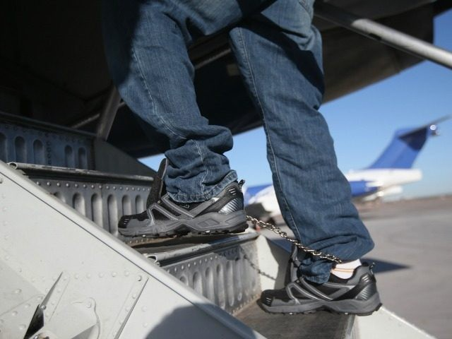 A Honduran immigration detainee, his feet shackled and shoes laceless as a security precaution, boards a deportation flight to San Pedro Sula, Honduras on February 28, 2013 in Mesa, Arizona.