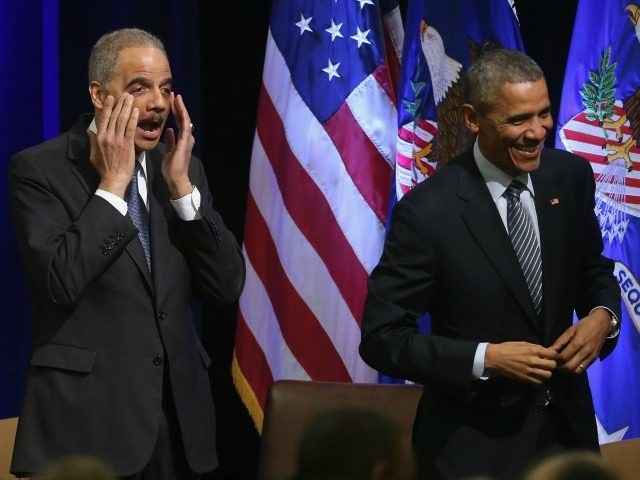 US President Barack Obama (R) and U.S. Attorney General Eric Holder react at the introduction of singer Aretha Franklin who sung during a farwell ceremony at the Justice Department February 27, 2015.