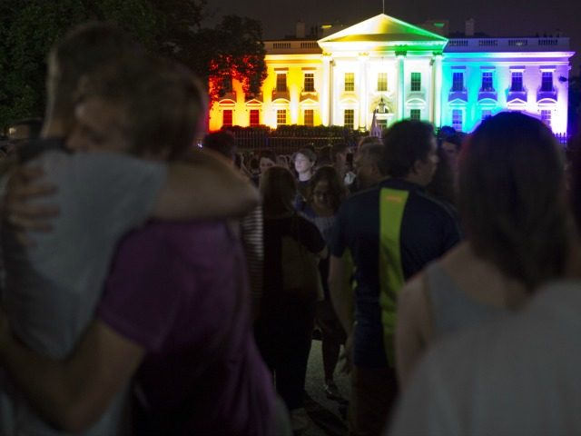 A gay couple hugs in front of the White House lightened in the rainbow colors in Washington on June 26. 2015.