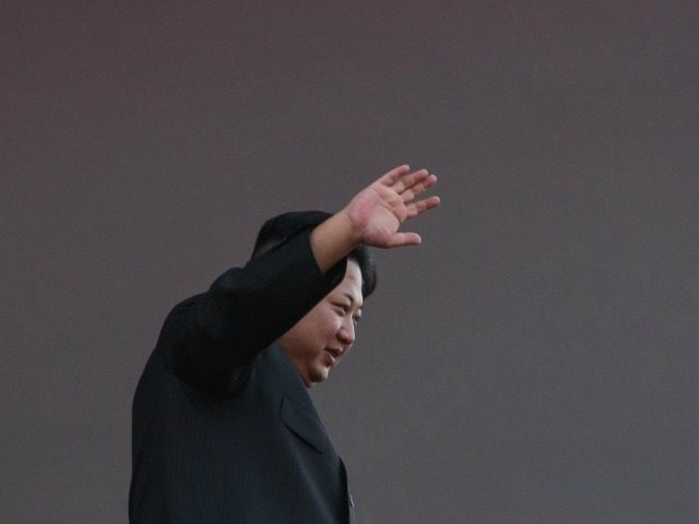 North Korea's leader Kim Jong-Un waves from a balcony towards participants of a mass military parade at Kim Il-Sung square in Pyongyang on October 10, 2015.