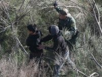 A Border Patrol agent leads juvenile undocumented immigrants after capturing them near the U.S.-Mexico border on December 10, 2015 at La Grulla, Texas.