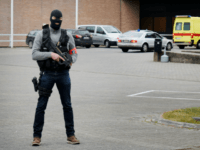 The ambulance believed to be transporting top Paris attacks suspect Salah Abdeslam arrives at the Bruges prison, on March 19 2016 as a police officer stands guard at the entrance of the prison.