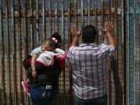 A family speaks through the U.S.-Mexico border fence on May 1, 2016 in Tijuana, Mexico.