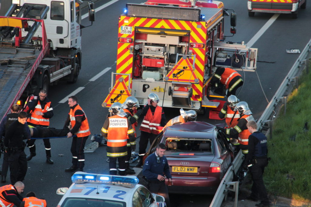 Rescue workers evacuate an injured person as police inspect the site of an accident on the A16 motorway in Coudekerque, near Dunkerque, northern France, on May 5, 2016. One person died and several were injured on early May 5 in three accidents which occurred on the A16 motorway near the French-Belgian border, including one involving a vehicle being persued by Belgian police. / AFP / LA VOIX DU NORD / Alexis Constant (Photo credit should read ALEXIS CONSTANT/AFP/Getty Images)