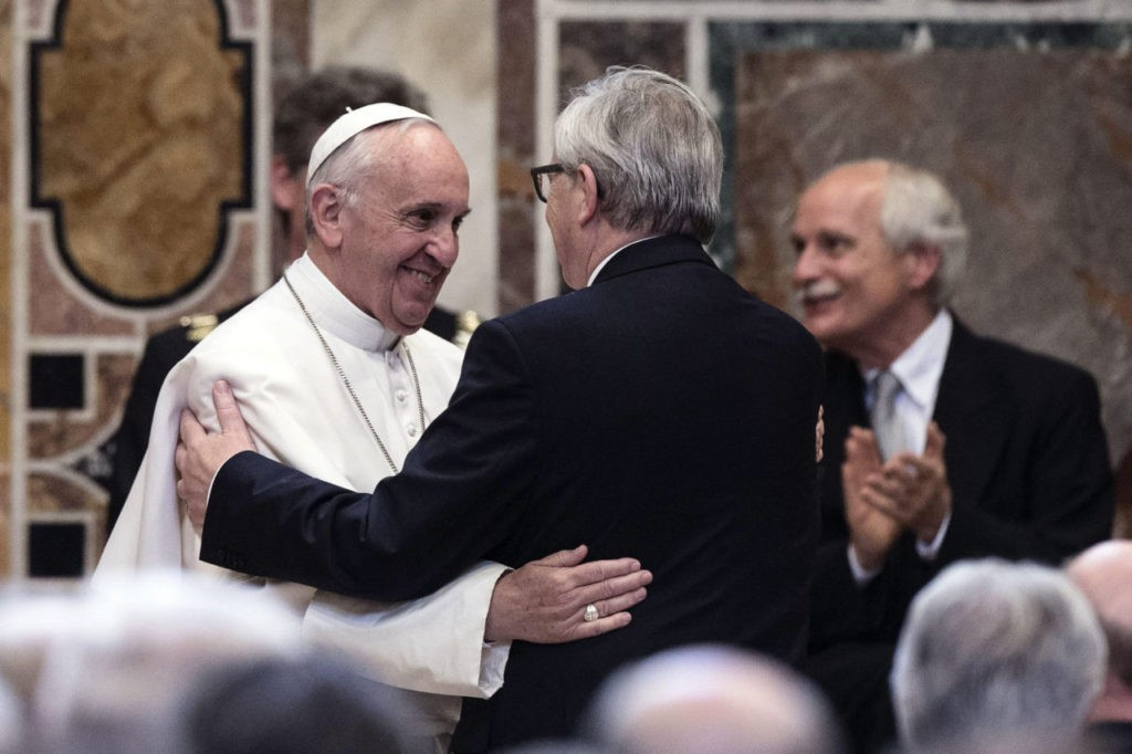 Pope Francis (L) is congratulated by European Commission President Jean-Claude Juncker (R) after receiving the European Union's Charlemagne Prize for his contribution to European unification, on May 6, 2016, at the Vatican. / AFP / OSSERVATORE ROMANO / ANGELO CARCONI (Photo credit should read ANGELO CARCONI/AFP/Getty Images)