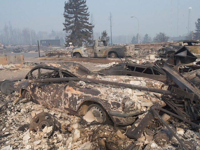FORT MCMURRAY, AB - MAY 06:  The remains of a classic Triumph GT6 sit in a residential neighborhood destroyed by a wildfire on May 6, 2016 in Fort McMurray, Alberta, Canada Wildfires, which are still burning out of control, have forced the evacuation of more than 80,000 residents from the town.  (Photo by Scott Olson/Getty Images)