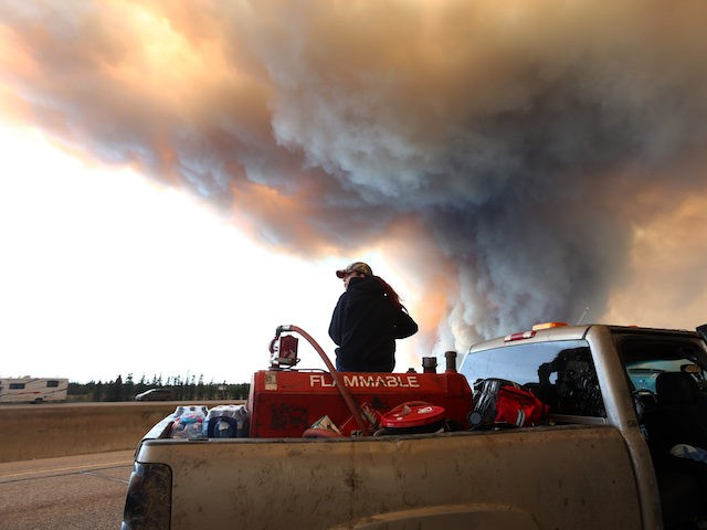 A group trying to rescue animals from Fort McMurray wait at road block on Highway 63 as smoke rises from a forest fire near Fort McMurray, Alberta on May 6, 2016. Canadian police led convoys of cars through the burning ghost town of Fort McMurray Friday in a risky operation …