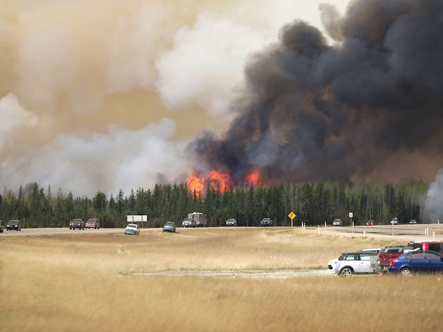 A convoy of evacuees drives  south as flames and smoke rises along the highway near  near Fort McMurray, Alberta on May 6, 2016.  Canadian police led convoys of cars through the burning ghost town of Fort McMurray Friday in a risky operation to get people to safety far to the south.In the latest chapter of the drama triggered by monster fires in Alberta's oil sands region, the convoys of 50 cars at a time are driving through the city at about 50-60 kilometers per hour (30-40 miles per hour) TV footage showed.  / AFP / Cole Burston/        (Photo credit should read COLE BURSTON//AFP/Getty Images)