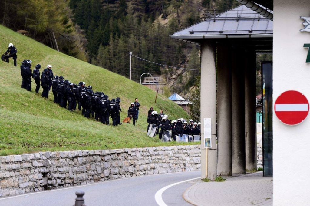 "Austrian police stand on a slope near the Brenner border as ""No border"" activists clash with Italian police (GIUSEPPE CACACE/AFP/Getty Images)"