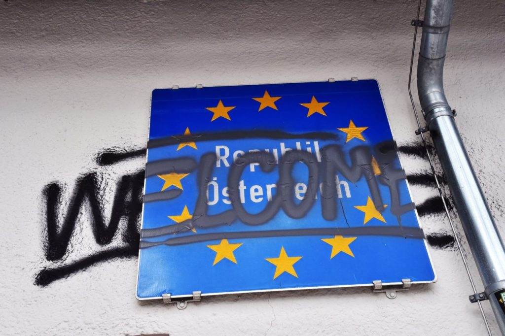 "A graffiti tag reads ""Welcome"" on a road sign for the Republic of Austria (GIUSEPPE CACACE/AFP/Getty Images)"