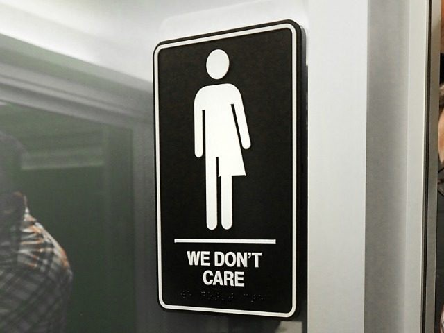 Museum manager Jeff Bell adheres informative backing to gender neutral signs in the 21C Museum Hotel public restrooms on May 10, 2016 in Durham, North Carolina.