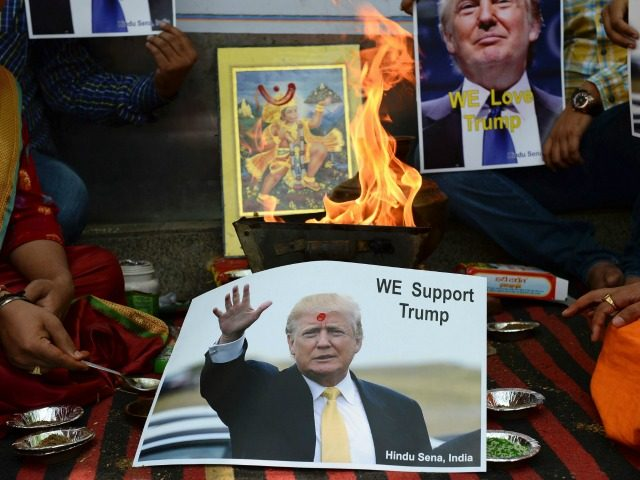 An Indian Hindu priest performs a Hawan (The Sarced Fire)ritual alongside posters bearing the image of US Republican presidential candidate Donald Trump in New Delhi on May 11, 2016. Right-wing Indian Hindu activists are holding a religious puja to help ensure victory for US Republican presidential candidate Donald Trump in …