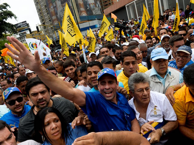 """Venezuelan opposition leader and Miranda State governor Henrique Capriles(L) is seen next to the president of the Venezuelan National Assembly Henry Ramos Allup (C white shirt) and the secretary general of the Democratic Unity Roundtable (MUD) Jesus """"Chuo"""" Torrealba (R) during a demostration in Caracas on May 11, 2016. With helmets, shields and bulletproof, military and Venezuelan police vests prevented Wednesday the advance of thousands of opponents who tried to reach the headquarters of the National Electoral Council (CNE), to demand accelerate the process of a recall referendum against President Nicolas Maduro. / AFP / FEDERICO PARRA (Photo credit should read FEDERICO PARRA/AFP/Getty Images)"""