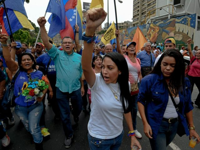 Members of the opposition of Venezuelan President Nicolas Maduro clash with riot police during a demonstration in Caracas on May 11, 2016. With helmets, shields and bulletproof, military and Venezuelan police vests prevented Wednesday the advance of thousands of opponents who tried to reach the headquarters of the National Electoral …