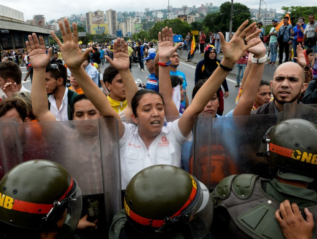 Opponents to the government of Venezuelan President Nicolas Maduro demonstrate in front of a line of riot police in Caracas on May 11, 2016. Riot cops fired tear gas to head off a protest march Wednesday by opponents of Venezuela's President Nicolas Maduro who were demanding a referendum on removing him from office. / AFP / FEDERICO PARRA (Photo credit should read FEDERICO PARRA/AFP/Getty Images)