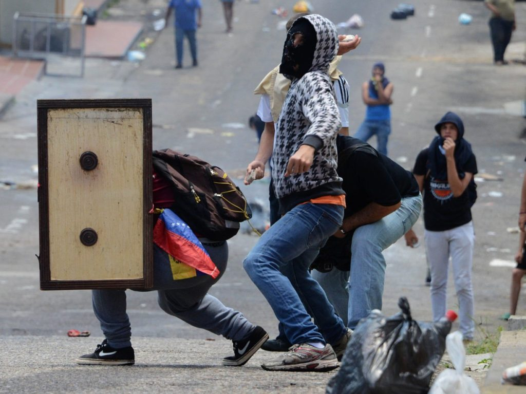 Venezuelan opposition activists clash with the police during a demonstration in San Cristobal, on May 11, 2016. Thousands of Venezuelan opposition took to the streets to demand the National Electoral Council (CNE) to accelerate the process of a recall referendum against President Nicolas Maduro. / AFP / George Castellanos (Photo credit should read GEORGE CASTELLANOS/AFP/Getty Images)