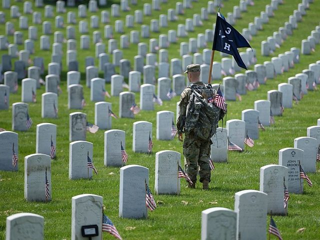 A member of the US Army looks on after placing American flags at graves at Arlington National Cemetery May 26, 2016 in Arlington, Virginia in preparation for Memorial Day. / AFP / Brendan Smialowski (Photo credit should read BRENDAN SMIALOWSKI/AFP/Getty Images)