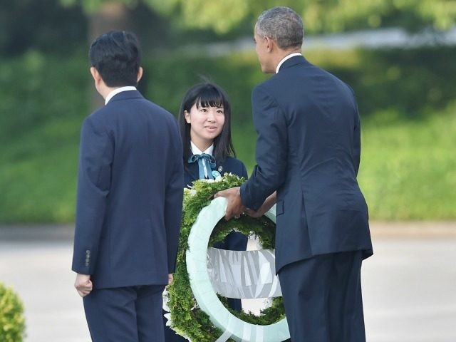 President Barack Obama (R) receives flowers to give as Japanese Prime Minister Shinzo Abe (L) looks on during U.S. President Obama's visit to the Hiroshima Peace Memorial Park on May 27, 2016 in Hiroshima, Japan.