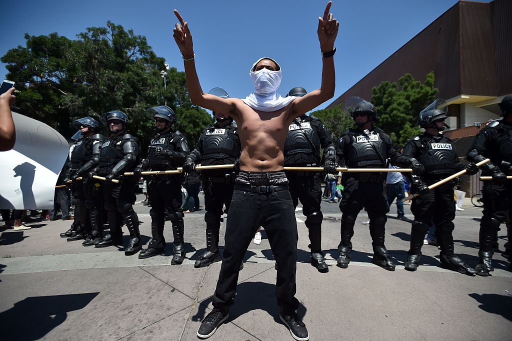 Carlos Moreno motions in front of a police skirmish line during a protest against republican presidential candidate Donald Trump who spoke at a rally in Fresno, California on May 27, 2016. / AFP / JOSH EDELSON (Photo credit should read JOSH EDELSON/AFP/Getty Images)
