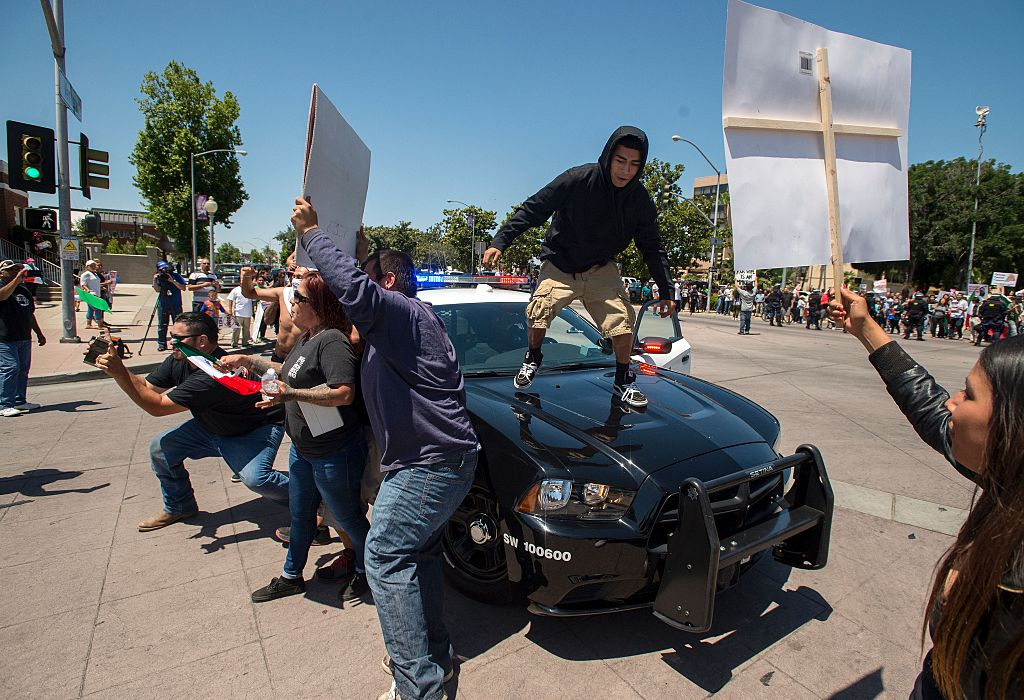 A protester jumps on a police car following a rally where republican presidential candidate Donald Trump spoke in Fresno, California on May 27, 2016. / AFP / JOSH EDELSON (Photo credit should read JOSH EDELSON/AFP/Getty Images)