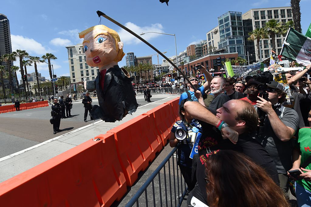Protesters hold up a pinata of republican presidential candidate Donald Trump as he speaks in San Diego, California on May 27, 2016. / AFP / Mark Ralston (Photo credit should read MARK RALSTON/AFP/Getty Images)