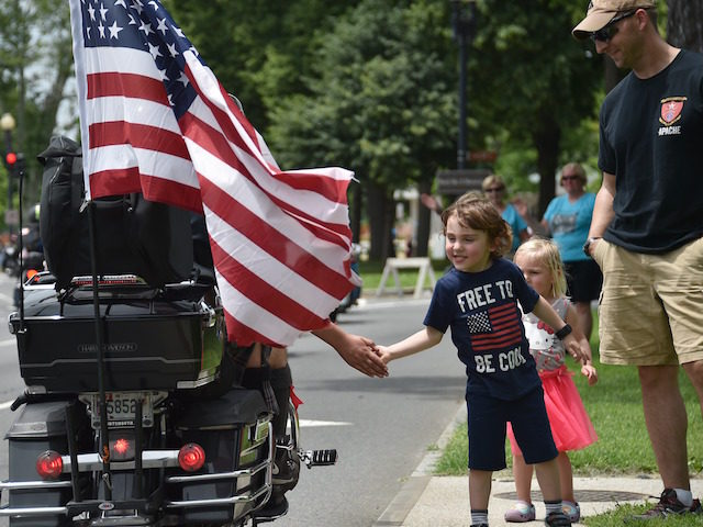 "A child greets motorcyclists during the annual Rolling Thunder ""Ride for Freedom"" parade ahead of Memorial Day in Washington, DC, on May 29, 2016. / AFP / MLADEN ANTONOV (Photo credit should read MLADEN ANTONOV/AFP/Getty Images)"