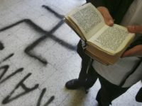 PETAH TIKVA, ISRAEL - MAY 4: A religious Jew recites prayers over a Swastika that desecrates the floor of the Grand Synagogue May 4, 2006 in Petah Tikva in central Israel. Jewish worshippers arriving for early morning prayers found the synagogue desecrated with Swastika and crucifix graffiti on its floors, …