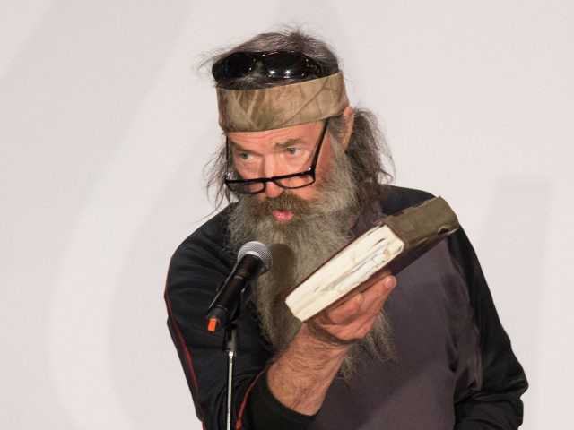 TV's Duck Dynasty star Phil Robertson holds up his Bible during a campaign rally for Republican presidential candidate Ted Cruz in Charleston, South Carolina, February 19, 2016. / AFP / JIM WATSON (Photo credit should read JIM WATSON/AFP/Getty Images)