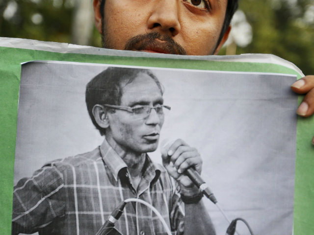 FILE- In this April 29, 2016 file photo, a Bangladeshi student holds a portrait of a University Professor A.F.M. Rezaul Karim Siddique during a protest against his killing in Dhaka, Bangladesh. Police have arrested four members of a banned militant group, including a regional commander, suspected in the killing last …