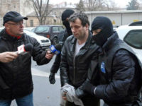 Marcel Lazar Lehel, 40, is escorted by masked policemen in Bucharest, after being arrested in Arad, 550 km (337 miles) west of Bucharest January 22, 2014. REUTERS/MEDIAFAX/SILVIU MATEI