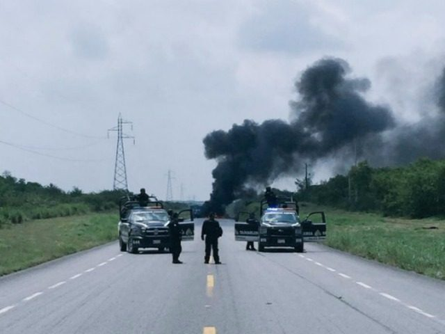 Mexican police keep a perimeter after cartel gunmen set fire to a truck in an effort to close a highway