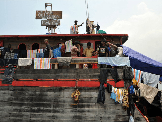 Sri Lankan asylum seekers stay on their boat moored at Merak seaport in Serang District on Indonesia's Java island, on October 22, 2009, after they were stopped by Indonesian authorities on their way to Australia. Australia's Prime Minister Kevin Rudd on October 22 angrily denied extremists were among hundreds of …