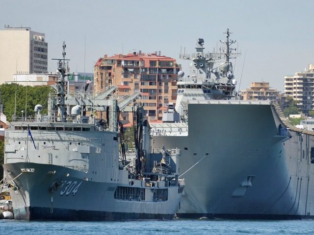 HMAS Canberra (R), the Royal Australian Navy's latest warship, is berthed at Garden Island naval base in Sydney on November 21, 2014. HMAS Canberra is the Royal Australian Navy's largest and most expensive warship and will be commissioned into service on November 28, 2014. AFP PHOTO/Peter PARKS (Photo credit should …