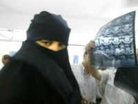 sick Palestinian woman wearing traditional clothing stands near German neurosurgeons who are treating her in Al-shifa hospital August 2, 2003 in Gaza City which is located in the Gaza Strip.