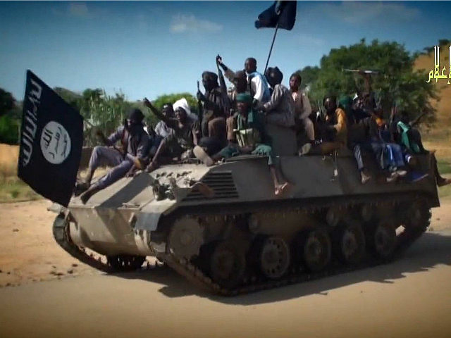 NIGERIA, Kano : A screengrab taken on November 9, 2014 from a new Boko Haram video released by the Nigerian Islamist extremist group Boko Haram and obtained by AFP shows Boko Haram fighters parading on a tank in an unidentified town. The leader of the Nigerian Islamist extremist group Boko Haram, Abubakar Shekau, dismissed again government claims about ceasefire talks and threatened to kill the man who has presented himself as Boko Haram's negotiator. AFP PHOTO / HO / BOKO HARAM