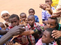 KENYA, DADAAB : DADAAB, KENYA - OCTOBER 12: This photo taken on October 4, 2014 shows refugee children reaching out for candies distributed by an African man at Dadaab refugee camp in Kenya, the largest refugee complex in the world, where thousands of Somalis, Tanzanians, Sudanese and Ethiopians fleeing conflicts …