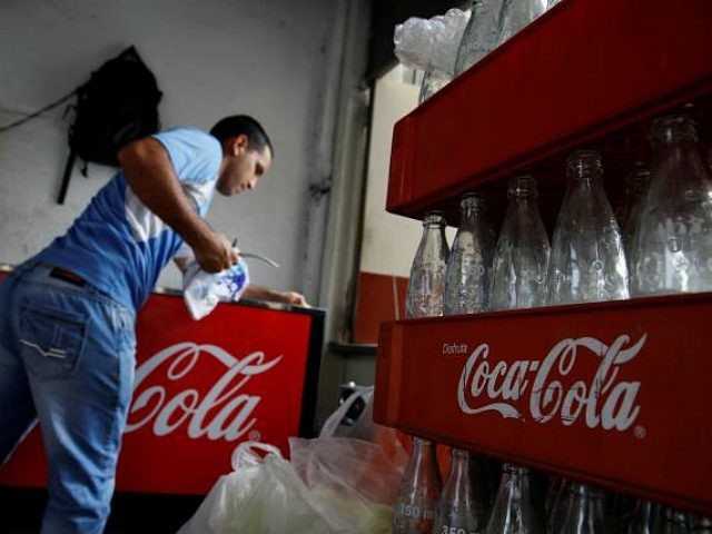 Cases of Coca-Cola with empty bottles are seen next to a man cleaning a fridge with the logo of the company, at a food stall on the street in Caracas, Venezuela May 24, 2016. REUTERS/CARLOS GARCIA RAWLINS