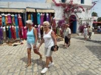 Tourists walk in the souk of Djerba on the Tunisian resort island on May 7, 2015.