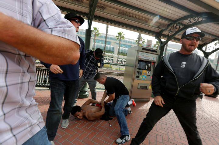 Police detain a man who was being chased by Trump supporters as supporters and anti-Trump demonstrators clash outside a campaign event for Republican U.S. presidential candidate Donald Trump in San Diego, California, U.S. May 27, 2016. REUTERS/David McNew