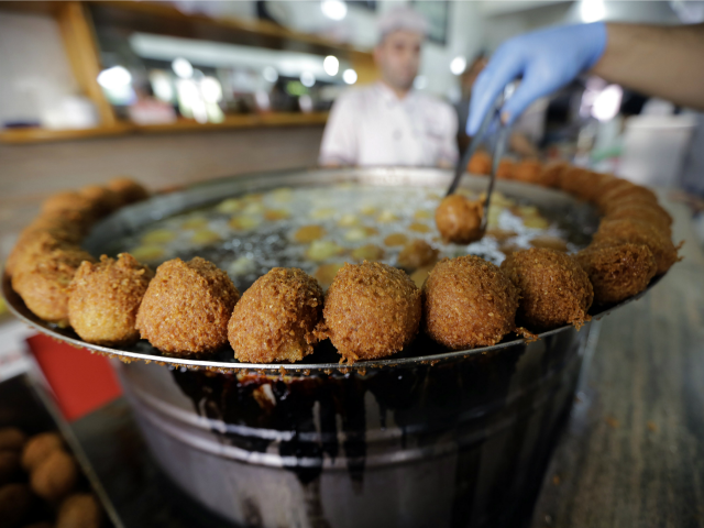 A cook fries Falafel balls at a restaurant in Jounieh, north of the Lebanese capital Beirut, on October 17, 2014.