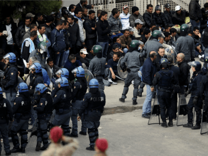 Police intervene to restore order in a temporary staying center, on the Italian island of Lampedusa, after migrants set fire and tried to escape, on April 11, 2011.